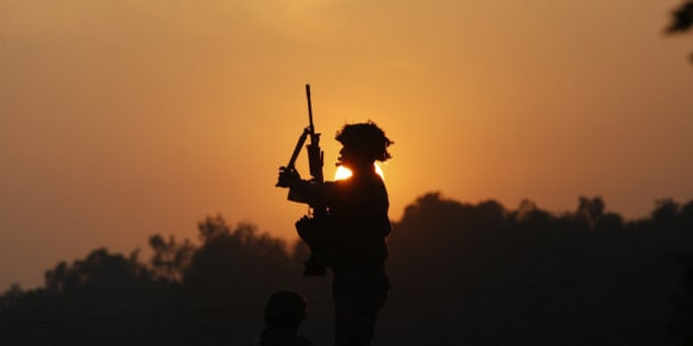 An Indian army soldier is silhouetted against the setting sun as he stands guard next to his colleague, sitting on the roof top of a house outside the Indian air force base in Pathankot, India, Sunday, Jan. 3, 2016. Indian troops were still battling at least two gunmen Sunday evening at the air force base near the country's border with Pakistan, more than 36 hours after the compound came under attack, a top government official said. (AP Photo/Channi Anand)