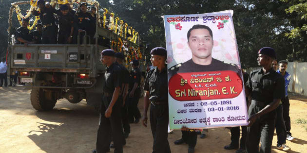 Indian army soldiers carry a portrait of  India's National Security Guard commando, Niranjan Kumar, who was among those killed in the attack on the Pathankot air force base after his body was brought to Bangalore, India, Monday, Jan. 4, 2016. At least two gunmen were holed up in a two-story building on the Indian air force base near the Pakistan border and exchanging gunfire with troops Monday, more than two days after they and several others attacked the heavily fortified compound, officials said. (AP Photo/Aijaz Rahi)