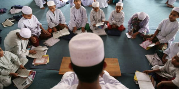 A madrasa, or Muslim religious school teacher teaches his students in Dhaka, Bangladesh, Sunday, April 19, 2009. Bangladesh's Prime Minister Sheikh Hasina sought the cooperation of Islamic leaders and scholars Saturday to fight against terrorism. (AP Photo/Pavel Rahman)