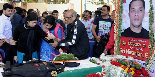 E.K. Sivaranjam (C), father of slain National Security Guard Bomb Disposal Squad personnel, thirty-four-year-old lieutenant colonel Niranjan Kumar, who died while defusing a grenade at the scene of a terror attack in Pathankot, consoles his daughter-in-law, K.G. Radhika (2L) on the arrival of Kumar's mortal remains at his residence in Bangalore on January 4, 2016.    Indian troops backed by helicopters searched an air force base January 4, after a weekend of fierce fighting with suspected Islamic insurgents in which seven soldiers and at least four attackers were killed.       AFP PHOTO / AFP / STR        (Photo credit should read STR/AFP/Getty Images)