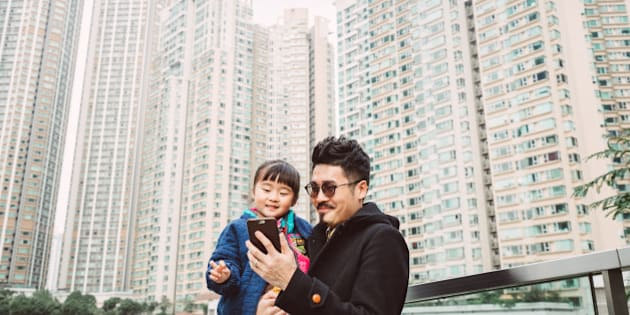 Young handsome dad carrying lovely little daughter while both having fun using a smartphone together joyfully on the roof garden which is surrounded by tall residential buildings in the city.