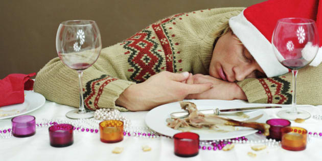 Young man in Santa hat sleeping at dinner table, resting head on arm