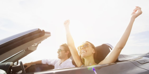 Couple driving in convertible under sunny sky