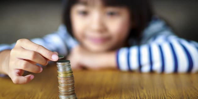 Little girl counts his coins on a table, select focus at coins.