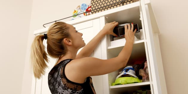 Young women looking into the top of a cupboard.