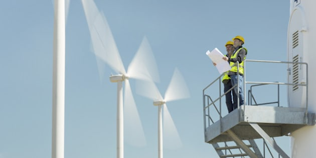 Workers standing on wind turbine in rural landscape