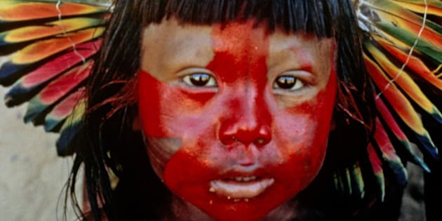 Kayapo boy with painted face and parrot-feather headdress; photographed in the Xingu Basin, Brazil.