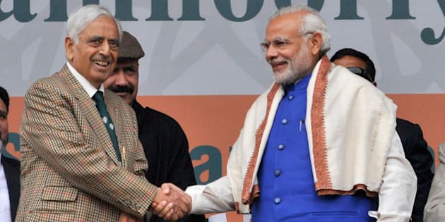SRINAGAR, INDIA - NOVEMBER 7: Prime Minister Narendra Modi greets Jammu & Kashmir Chief Minister Mufti Mohammad Sayeed during a rally at the Sher-i-Kashmir cricket Stadium on November 7, 2015 in Srinagar, India. Modi announced a special package of Rs. 80,000 crore for Jammu and Kashmir and said that the government's treasury is for the people. He said, 'If we can develop this, the youth will find employment right here. Friends, this development, in Jammu, Kashmir or Ladakh will always be our top agenda. And I dream of a new powerful, resurgent Kashmir.' (Photo by Waseem Andrabi/Hindustan Times via Getty Images)