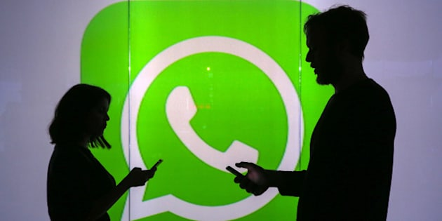 People are seen as silhouettes as they check mobile devices whilst standing against an illuminated wall bearing WhatsApp Inc's logo in this arranged photograph in London, U.K., on Tuesday, Jan. 5, 2016. WhatsApp Inc. offers a cross-platform mobile messaging application that allows users to exchange messages. Photographer: Chris Ratcliffe/Bloomberg via Getty Images