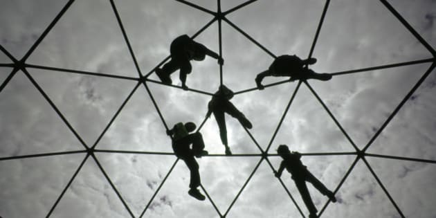 Ethnically diverse young boys and girls silhouetted against the sky while playing and climbing together on a playground Jungle Jim.