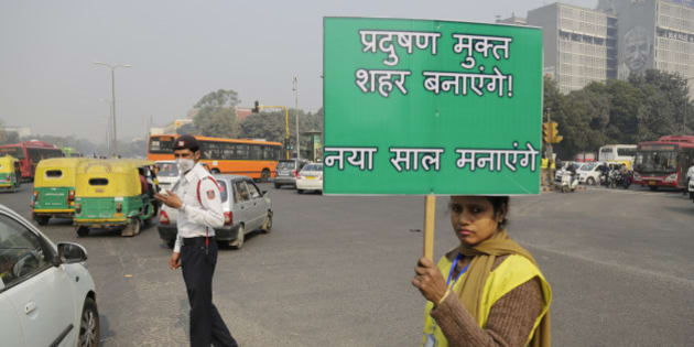 """A volunteer holds a placard which reads """"We will make a pollution free city"""" at a traffic intersection usually congested, on the first day of a two-week experiment to reduce the number of cars to fight pollution in New Delhi, India, Friday, Jan. 1, 2016. The volunteers are meant to encourage people to fall in line with the government's plan to allow private cars on the roads only on alternate days from Jan. 1-15, depending on whether their license plates end in an even or an odd number. (AP Photo/Altaf Qadri)"""