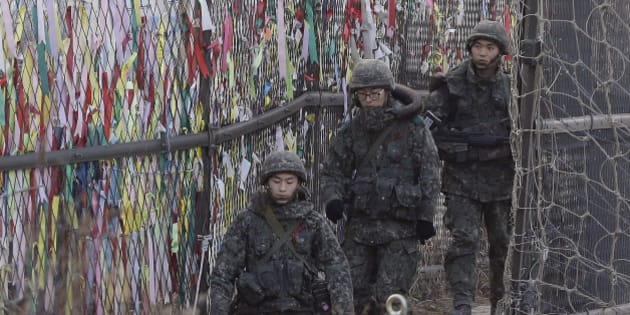 South Korean army soldiers patrol by ribbons, wishing for the reunification of the two Koreas, attached on the barbed-wire fence in Paju, near the border with North Korea, South Korea, Wednesday, Jan. 6, 2016. North Korea said it conducted a powerful hydrogen bomb test Wednesday, a defiant and surprising move that, if confirmed, would be a huge jump in Pyongyang's quest to improve its still-limited nuclear arsenal. (AP Photo/Ahn Young-joon)