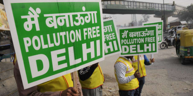 NEW DELHI, INDIA - JANUARY 1: Volunteers holding placards on the first day of Delhi's Odd-Even Vehicle Plan, on January 1, 2016 in New Delhi, India. The odd-even scheme that allows odd and even-numbered private vehicles to ply on city roads on alternate days aims at reducing air pollution levels. All diesel and petrol cars, irrespective of where they are coming from, will have to follow the rules. If a car is coming from out of Delhi and is breaking the odd-even rule, a fine will be levied. The government has deployed hundreds of volunteers and 3000 buses to help traffic police. To clean the Capital's toxic air, only odd-numbered private cars will be allowed on the road on odd dates and even-numbered on even days. Violators face a fine of Rs. 2,000. (Photo by Burhaan Kinu/Hindustan Times via Getty Images)