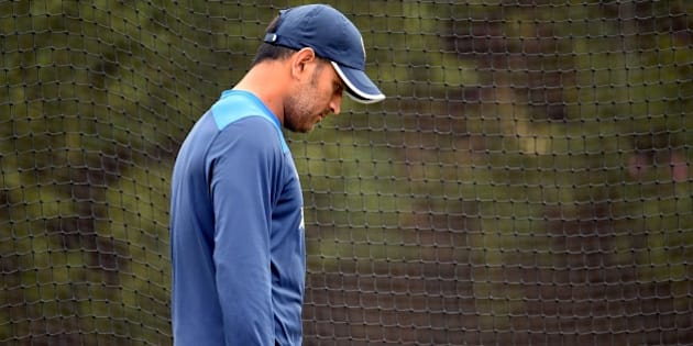 Former Indian captain M.S. Dhoni walks past the nets during cricket training at the Sydney Cricket Ground (SCG) on January 5, 2015.  Australia are preparing to take on India in the fourth cricket Test starting on January 6.  AFP PHOTO / William WEST  