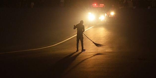 The silhouette of an Indian labourer is seen against the lights of military police car as he sweeps the road after the rehearsal of the Beating Retreat Ceremony at Vijay Chowk in New Delhi on January 27, 2015. The ceremony is a culmination of Republic Day celebrations and dates back to the days when troops disengaged themselves from battle at sunset. AFP PHOTO / CHANDAN KHANNA        (Photo credit should read Chandan Khanna/AFP/Getty Images)