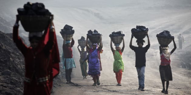 JHARKHAND, INDIA - DECEMBER 06: Villagers carry illegally scavenged coal from an open-cast coal mine in Dhanbad, Jharkhand, India on December  6, 2014, trying to earn a few dollars a day. Indian government lead by Prime Minister Narendra Modi plans to double its coal production by 2019. (Photo by Kuni Takahashi/Getty Images)