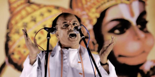 BANGALORE, INDIA:  Vishwa Hindu Parishad (VHP,World Hindu Council) international secretary Pravin Togadia gestures whilst standing in front of a billboard with a painting depicting the Hindu Monkey God Hanuman as he addresses a rally in Bangalore, 07 December 2003 .  Togadia urged those attending the rally to support the cause for the reconstruction of the Ram Temple in Ayodhya.  In 1992 Hindu fundamentalists razed a 16th century mosque to the ground in the Northern Indian town, which they claimed was built on the site of the birthplace of the Hindu God Ram.   AFP PHOTO/Indranil MUKHERJEE  (Photo credit should read INDRANIL MUKHERJEE/AFP/Getty Images)