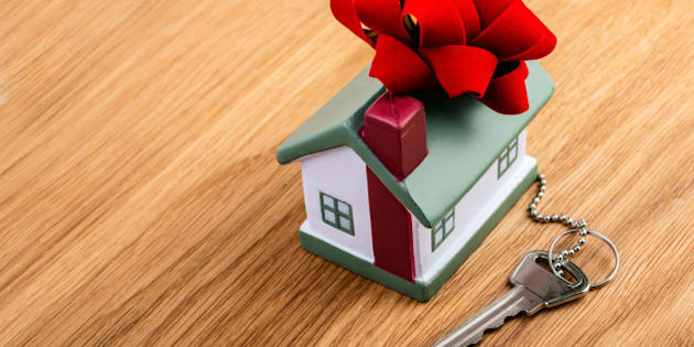 house with red ribbon and key on wooden background