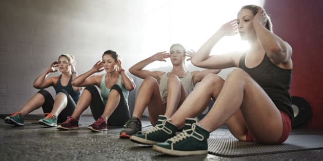 Four young women fitness training, doing sit-ups together in urban industrial gym.