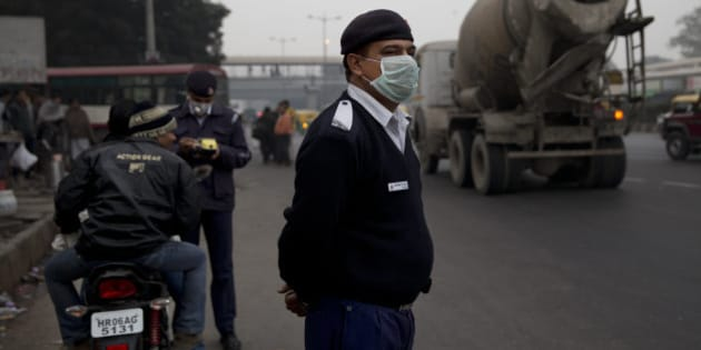 An Indian traffic policeman wears a mask as he stands on a road in New Delhi, India, Wednesday, Jan. 6, 2016. The Indian capital is currently testing a formula to reduce its record-high air pollution by limiting the numbers of cars on the streets for two weeks.(AP Photo /Tsering Topgyal)