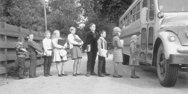 Line of children at bus stop getting on the school bus, Birmingham, Michigan, November 5, 1966. (Photo by Camerique/Getty Images)