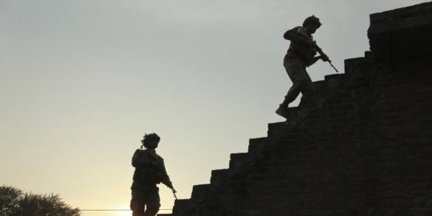 Indian army soldiers climb up the stairs of a residential building outside the Indian air force base in Pathankot, India, Sunday, Jan. 3, 2016. Indian troops were still battling at least two gunmen Sunday evening at the air force base near the country's border with Pakistan, more than 36 hours after the compound came under attack, a top government official said. (AP Photo/Channi Anand)
