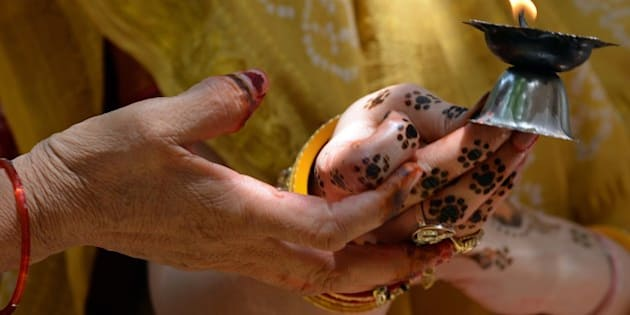 An elderly lady holds the henna-decorated hands of a married Hindu woman as they offer prayers with an oil lamp on the occasion of 'Vata Savitri Poornima' in Mumbai on June 12, 2014. On the occasion of Vata Savitri Purnima married Hindu women keep a fast for the long-life and good health of their husbands and break their fast by performing rituals beneath a banyan tree. The day's ritual involves worshipping a banyan (vata) tree by applying holy 'red kumkum' (vermillion) and turmeric and placing flowers and lighting incense sticks reverentially and culminates with the women circumambulating the tree seven times round, unwinding a spool of white thread in their hands as a priest recites mantras.  AFP PHOTO/ INDRANIL MUKHERJEE        (Photo credit should read INDRANIL MUKHERJEE/AFP/Getty Images)