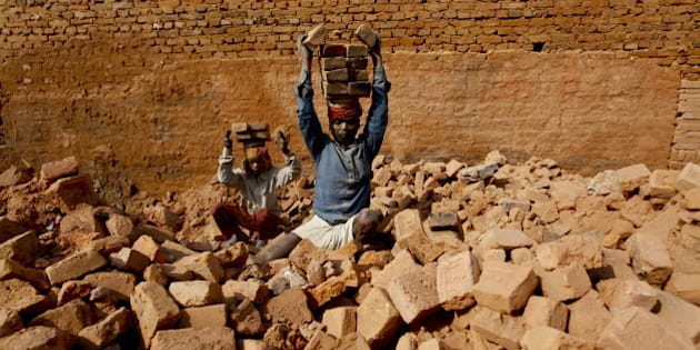 LALITPUR, January 11, 2016 :  Indian seasonal migrant laborers carry raw bricks at a brick factory in Harisidhhi, Lalitpur, Nepal, January 11, 2016. Thousands of migrant laborers from India and Nepal arrived in Nepal to work. The demand for bricks is high in Kathmandu after more than 30 million houses were damaged due to the 2015 April Earthquake. (Xinhua/Pratap Thapa via Getty Images)