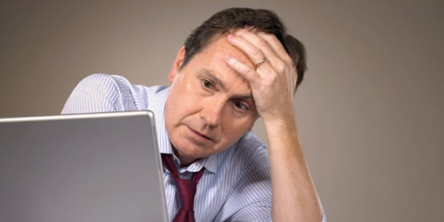 Businessman sitting at laptop by screwed up paper, head on hand