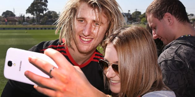 MELBOURNE, AUSTRALIA - SEPTEMBER 05: Dyson Heppell of the Bombers poses for a selfie with a fan during an Essendon Bombers AFL training session at True Value Solar Centre on September 5, 2014 in Melbourne, Australia.  (Photo by Michael Dodge/Getty Images)