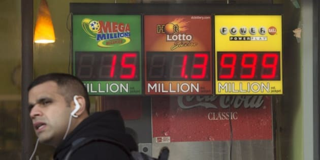 A man walks past a sign showing a Powerball prize of $999 million, the largest jackpot winnings that the Powerball sign can display, with the actual Powerball jackpot estimated at $1.3 billion, outside a deli in Washington, DC, January 11, 2016. The jackpot for the US Powerball lottery rose to a whopping $1.3 billion (1.19 billion euros) on January 10, by far the largest in US history, after organizers said there was no winner in the weekend draw. The Powerball prize rocketed to $950 million on Saturday, fueling a frenzy of lotto ticket buying across the United States. Numbers were drawn and announced late Saturday at 10:59 pm (0359 GMT Sunday) -- but hours later lottery officials said there was no winner. AFP PHOTO / SAUL LOEB / AFP / SAUL LOEB        (Photo credit should read SAUL LOEB/AFP/Getty Images)