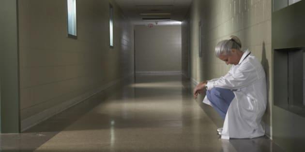 'Female doctor sitting in hospital corridor, side view'