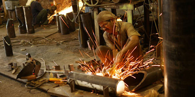 Men working with an angle grinder as it sprays sparks inside a metalworking factory in the docks are of Mumbai.