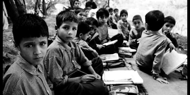 The students at school. This class has students from beginners to about 4th grade. At the end is the teacher. Sitting underneath maple trees bordering the apple orchards, they learn everything from Urdu to counting. Their school building was shelled in December 2006 and has not been repaired yet. Pattan sub-division, Kashmir.