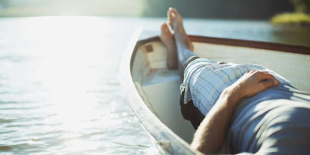 Man laying in rowboat on tranquil lake