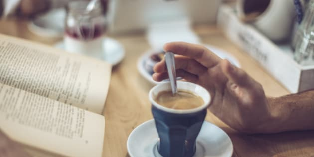 Young man drinking coffee in a cafe. Close-up.