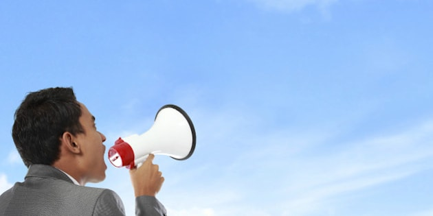 business man shouting using megaphone under the blue sky