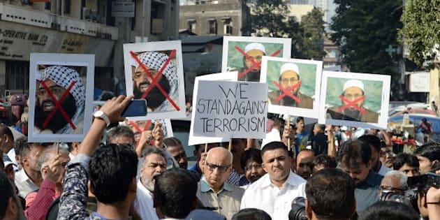 Indian activists carry photographs of the chief of Jaish-e-Mohammad, Maulana Masood Azhar (L) and chief of Pakistan's outlawed Islamic hardline Jamaat ud Dawa (JD), Hafiz Mohammad Saeed (R) during a protest against the attack on the air force base in Pathankot, in Mumbai on January 4, 2016.  Indian troops backed by helicopters searched an air force base January 4, after a weekend of fierce fighting with suspected Islamic insurgents in which seven soldiers and at least four attackers were killed.    AFP PHOTO/ Indranil MUKHERJEE / AFP / INDRANIL MUKHERJEE        (Photo credit should read INDRANIL MUKHERJEE/AFP/Getty Images)