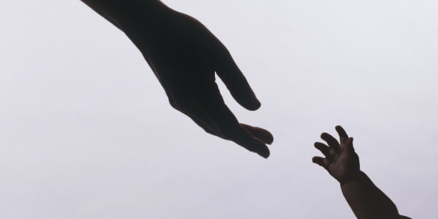 Silhouette of baby's hands reaching for mothers'