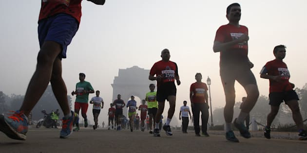 NEW DELHI, INDIA - NOVEMBER 29: Runners take part in Airtel Delhi Half Marathon 2015 at Rajpath in the foggy weather on November 29, 2015 in New Delhi, India. This year Delhi half marathon saw huge participation from countries like Kenya, Ethiopia and Uganda in elite category. Birhanu Legese from Ethiopia and Cynthia Limo of Kenya won the elite men and women categories of Delhi half marathon. Nitendra Singh Rawat and Lalita Babbar bagged the title of the fastest Indian man and woman respectively. (Photo by Raj k Raj/Hindustan Times via Getty Images)