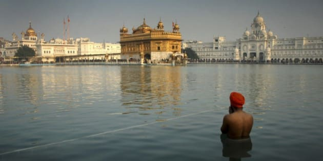 An Indian Sikh devotee takes a holy dip in the sacred pond at the Golden Temple in Amritsar, India, Wednesday, Jan. 1, 2014. Thousands of Sikh devotees stand in a queue to pay obeisance at the Golden Temple, Sikhs' holiest shrine, on the first day of the New Year. (AP Photo/Sanjeev Syal)