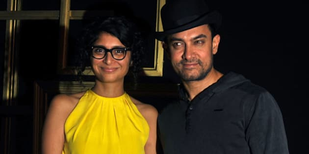 Indian Bollywood actor Aamir Khan (R) poses with his wife Kiran Rao as they arrive to attend a party hosted by actress Deepika Padukone in Mumbai late December 21, 2013.  AFP PHOTO/STR        (Photo credit should read STRDEL/AFP/Getty Images)