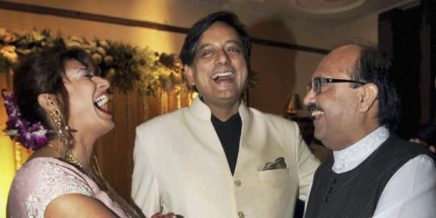 Former Indian Junior Foreign Minister Shashi Tharoor, center, and his wife Sunanda Pushkar are greeted by Indian lawmaker Amar Singh at their wedding reception in New Delhi, India, Saturday, Sept. 4, 2010. Tharoor resigned from his post earlier this year amid allegations of corruption in the bidding for an Indian premier league team at auction in April that also involved his friend and businesswoman Pushkar. (AP Photo)