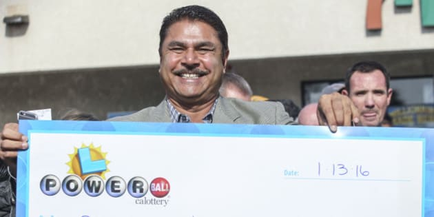 CHINO HILLS,  CA- JANUARY 14:  Balbir Atwal, owner of the California 7-Eleven that sold one of the 3 Powerball winning tickets, holds up a $1 million check after received from the California State Lottery, in front of his store on January 14, 2016 in Chino Hills, California.   Winning tickets were also sold in Florida and Tennessee and will share an  estimated record-breaking $1.58 billion dollar jackpot.  (Photo by Ringo Chiu/Getty Images)