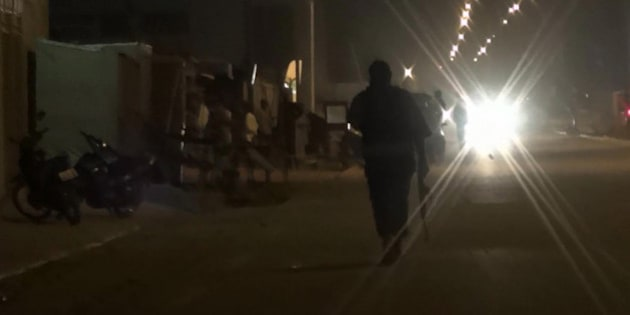 In this grab taken from video by Associate Press Television, an armed policeman patrols the area after an attack on a hotel,  in Ouagadougou, Burkina Faso, Friday, Jan. 15, 2016.  Attackers struck an upscale hotel popular with Westerners in Burkina Faso's capital late Friday, fueling the recent political turmoil in the West African country. Three hours later, gunfire could still be heard as soldiers in an armored vehicle finally approached the area. (Associated Press Television via AP)