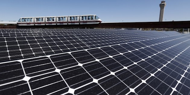 Solar panels that were recently placed on the roof of the building supplying energy to the AirTrain at Newark Liberty International Airport are seen as the train rolls by, Thursday, April 24, 2014, in Newark, N.J. According to The Port Authority of NY and NJ, the 3,200-solar panel installation spread among four building rooftops will supply the airport with 0.7 MW, equivalent to powering 61 homes with electricity, conserving 992 barrels of oil or removing 90 passenger vehicles from the road each year. (AP Photo/Julio Cortez)