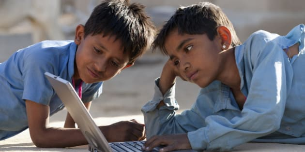 India, Rajasthan, two young boys using laptop computer