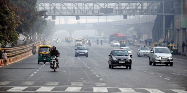 NEW DELHI, INDIA - JANUARY 1: Less traffic seen on the roads on the first day of Delhi's Odd-Even Vehicle Plan, on January 1, 2016 in New Delhi, India. The odd-even scheme that allows odd and even-numbered private vehicles to ply on city roads on alternate days aims at reducing air pollution levels. All diesel and petrol cars, irrespective of where they are coming from, will have to follow the rules. If a car is coming from out of Delhi and is breaking the odd-even rule, a fine will be levied. The government has deployed hundreds of volunteers and 3000 buses to help traffic police. To clean the Capital's toxic air, only odd-numbered private cars will be allowed on the road on odd dates and even-numbered on even days. Violators face a fine of Rs. 2,000. (Photo by S Burrmaula/Hindustan Times via Getty Images)
