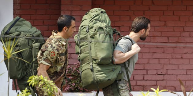 Italian marines, Massimiliano Latorre, left, and Salvatore Girone, walk with their backpacks towards a waiting police vehicle to be taken to court outside the guesthouse where they have been kept in police custody in Kochi, India, Thursday, March 1, 2012. The two Italian marines are accused of fatally shooting two Indian fishermen off southwest India. The marines were providing security on a cargo ship and mistook the fishermen for pirates. New Delhi has said the Italians should be tried in India because the killings happened on an Indian boat. Rome has argued the shooting took place in international waters and the case should be handled in Italy. (AP Photo/Aijaz Rahi)