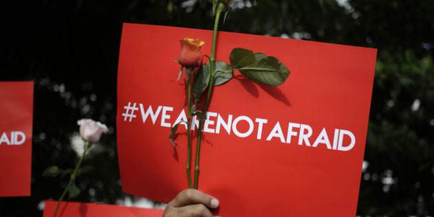 An activist holds a poster during a rally condemning Thursday's attack, outside the Starbucks cafe where it took place in Jakarta, Indonesia, Friday, Jan. 15, 2016. Indonesians were shaken but refusing to be cowed a day after a deadly attack in a busy district of central Jakarta that has been claimed by the Islamic State group. (AP Photo/Dita Alangkara)